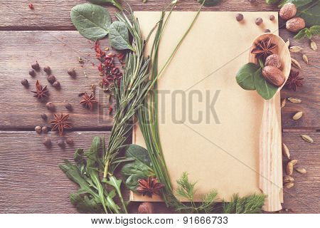 Recipe book page with spoon and different herbs on wooden background