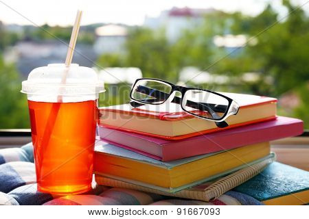 Books, glasses and drink on windowsill