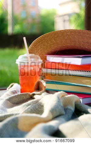 Books, hat and drink outdoors