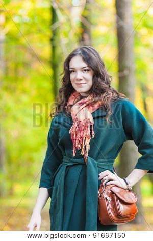Stylish Caucasian Female Brunette Model Posing In Autumn Forest And Smiling