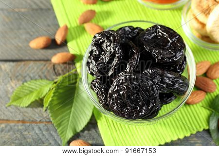 Dried fruits and almonds with leaves on green napkin, closeup