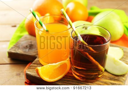 Assortment of healthy fresh juices and fruits on wooden table background