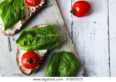 Delicious sandwiches with tomatoes and greens on cutting board on table close up