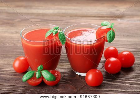 Glasses of tomato juice with vegetables on wooden background