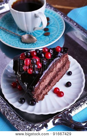 Delicious chocolate cake with berries and cup of coffee on table close up