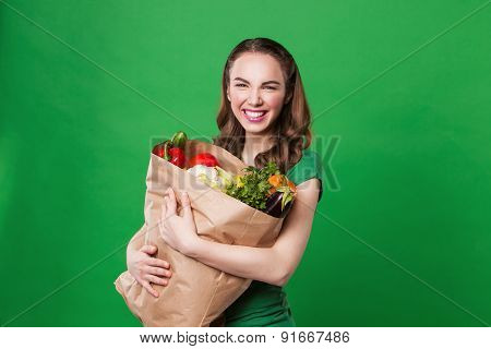 young woman holding a grocery bag full of fresh and healthy food. on green background