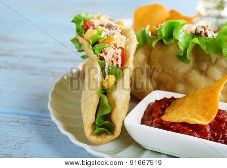Tasty taco with tomato dip on plate and vegetables on table close up