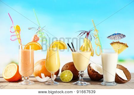 Summer cocktails on wooden table on bright blurred background