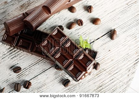 Stuffed chocolate with coffee beans and mint on wooden table, top view