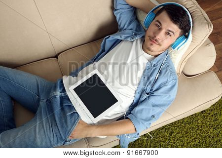 Handsome young man lying on sofa and listening to music in room