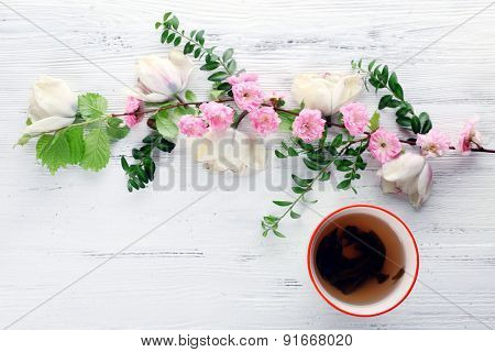Cup of tea with beautiful flowers on wooden background