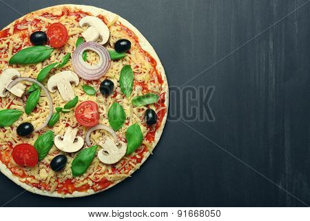 Raw pizza with vegetables on wooden background