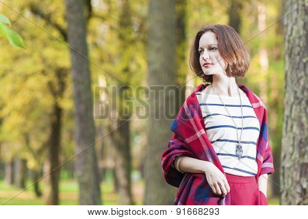Female Style Concept: Caucasian Brunette Woman Posing In Autumn Forest Outdoors