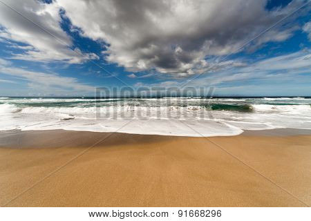 Sand beach and clouds over sea