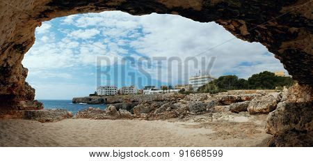 View from natural cave of stone shore and hotels, Majorca. Spain