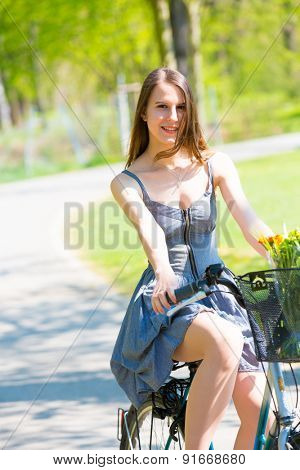 Young woman in short grey dress with long hair rides a bicycle with basket and flowers tour summer city park, look and smile on at camera