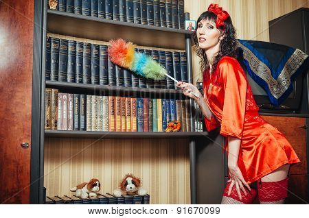 Portrait of a young beautiful housewife playing with  duster and smiling
