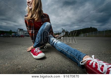 Young smiling lady sitting on the skateboard
