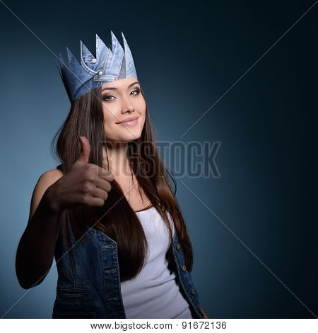Pretty jeans princess. Beautiful girl in jeans and paper crown with thumb up over blue background.