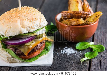 Serving Homemade Burger With Potato Wegdes On Wooden Table