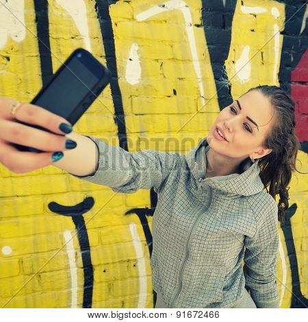 Happy attractive girl with smart phone takes selfie against urban grunge graffiti wall, toned.