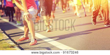 Marathon runner stretching legs on city road