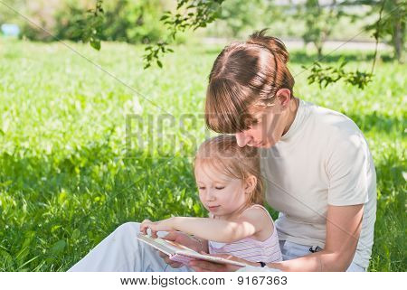 Mother And Daughter Sitting On The Grass And Looking Book