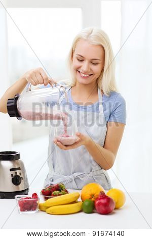 healthy eating, cooking, vegetarian food, dieting and people concept - smiling young woman putting fruits for fruit shake to blender shaker at home