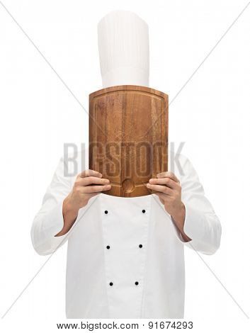 cooking, profession and people concept - male chef cook covering face or hiding behind wooden cutting board