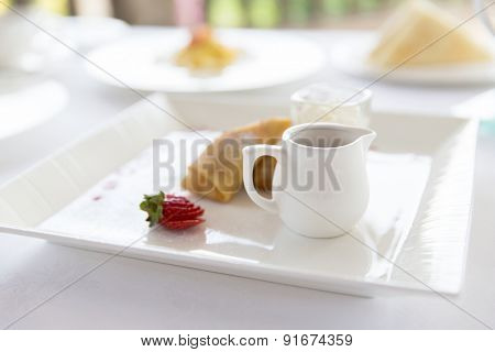 food, dessert, morning and eating concept - close up of plate with pancakes and honey or jam on table