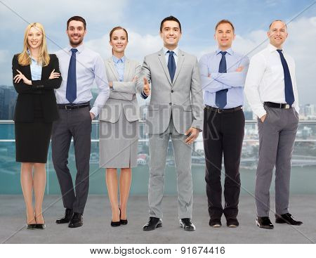 business, people, gesture and office concept - group of smiling businessmen making handshake over city background