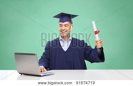 education, graduation, technology and people concept - happy adult student in mortarboard with diploma and laptop computer sitting at table over green school chalk board background