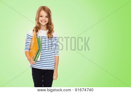 education, people, children and school concept - happy girl holding colorful folders over green background