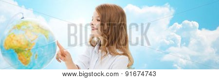 education, school, people, childhood and school concept - smiling little student girl with globe over green chalk board background