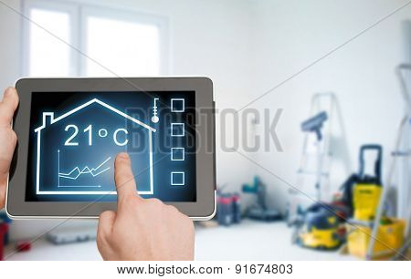 home, housing, people and technology concept - close up of man hands pointing finger to tablet pc computer and regulating room temperature over storeroom or building background