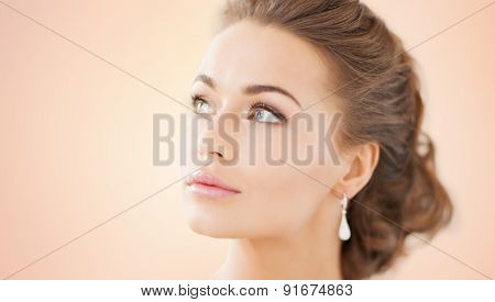 people, beauty, jewelry and accessories concept - beautiful woman with diamond earrings over beige background