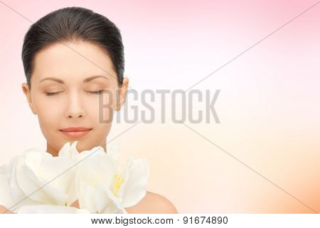 beauty, people, holidays and health concept - beautiful young woman smelling flowers with closed eyes over pink background