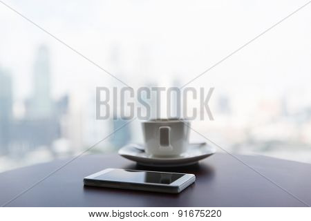 technology, business and modern life concept- close up of smartphone and coffee cup on table at office or hotel room
