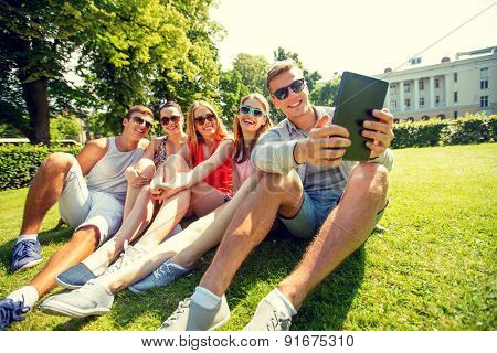 friendship, leisure, summer, technology and people concept - group of smiling friends with tablet pc computer sitting and making selfie in park