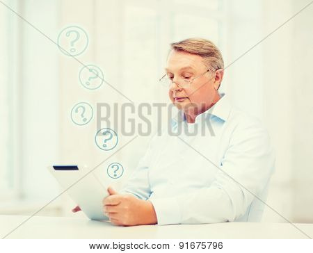 business, office, oldness, school and education concept - old man wearing eyeglasses with tablet computer at home