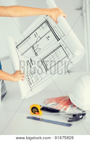 architecture and home renovation concept - woman with blueprint, flexible ruller, helmet and hammer