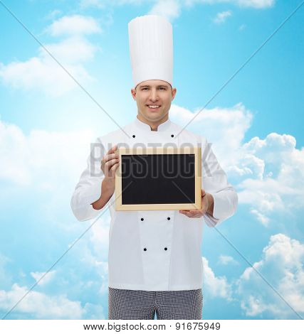 cooking, profession, advertisement and people concept - happy male chef cook showing and holding blank menu board over blue sky with clouds background