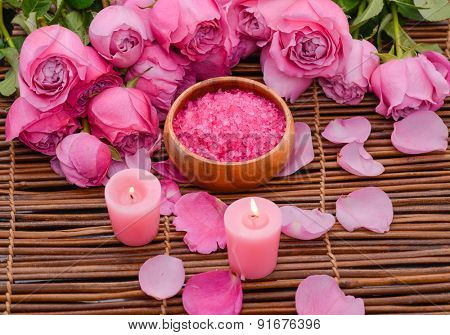 Lying down rose with salt in bowl and candle on mat