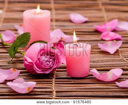 Pink rose with two candle and petals on mat