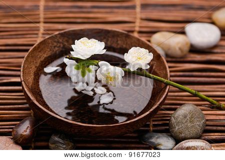 White Cherry flower on wooden bowl with pile stones on mat