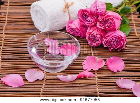 White towel ,bowl and lying down rose, Petals on mat