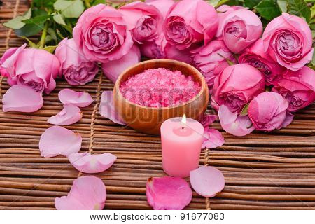 Pink rose with pink candle and petals, salt in bowl on mat
