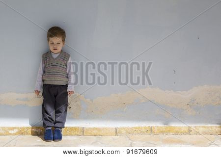Portrait of a small boy on the old blue wall