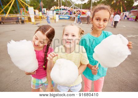 Cute girls eating cotton candy outdoors