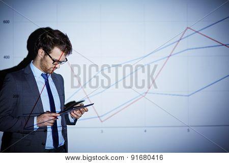 Handsome businessman with touchpad preparing presentation